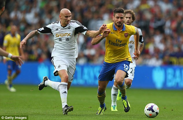 Hunted down: Olivier Giroud is tracked by Jonjo Shelvey as he tries to make progress