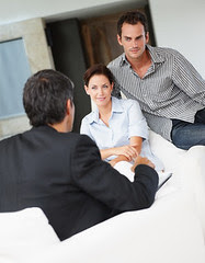 Happy young couple in discussion with a financ...