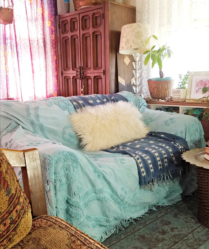 old sofa covered in turquoise hand dyed bed coverlet with indigo mudcloth and mongolian fur pillow- hand me down sofa done bohemian
