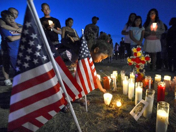 21 de julho - Magan Saving acende velas por vítimas do ataque. Vigília foi feita trás do cinema onde a tragédia aconteceu (Foto: Jeremy Papasso/Reuters)
