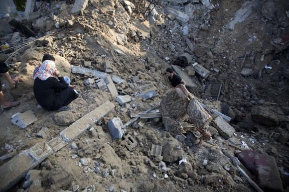 Un palestino recoge un mueble de entre los escombros de una casa destruida por Israel en Beit Hanu, al norte de la Franja de Gaza