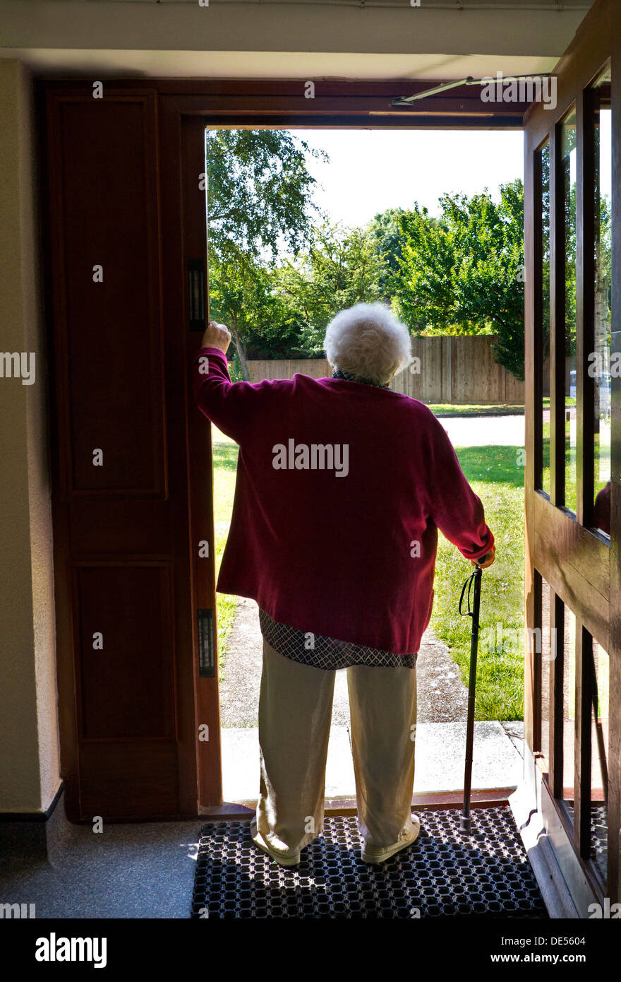 pensive elderly senior old age lady standing alone with walking stick DE5604