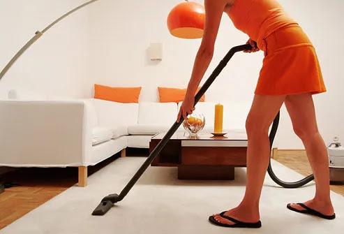 Woman vacuuming living room rug