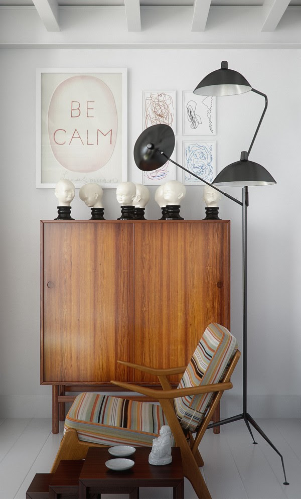 A pairing of a classic danish modern chair and cabinet in rich wood add warmth to
