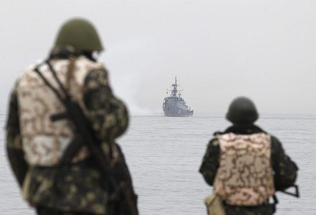 Soldados ucranianos observam navio de guerra russo em Sebastopol