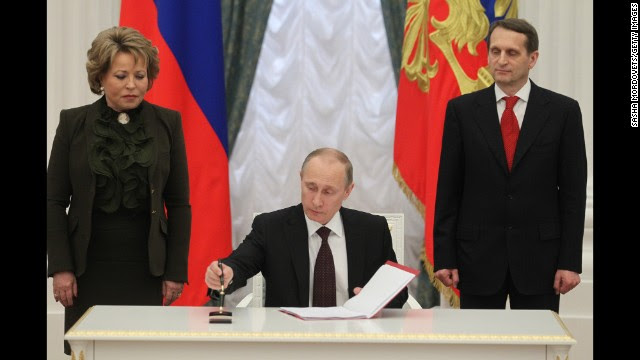 Russian President Vladimir Putin signs the final decree completing the annexation of Crimea in Moscow on Friday, March 21, as Upper House Speaker Valentina Matviyenko, left, and State Duma Speacker Sergei Naryshkin, right, watch. Russia's military activities in Crimea and its move to annex the region have been condemned by Ukraine's interim government in Kiev, the European Union and the United States. The standoff has sparked an international crisis, reviving concerns of a return to Cold War relations.