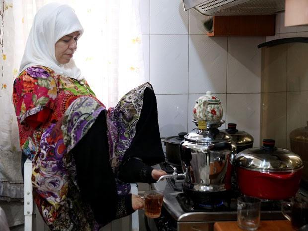 Zohreh Etezadossaltaneh usa um apoio quando vai cozinhar (Foto: Ebrahim Noroozi/AP)