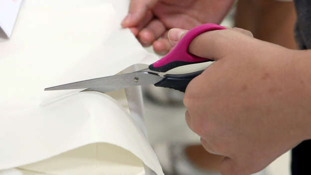 A person cuts paper with scissors for left-handed.