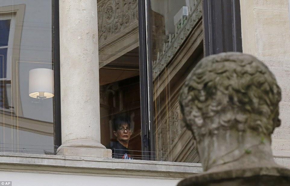 A mulher olha para fora de uma janela da residência de Kim Kardashian Ocidente em Paris na segunda-feira