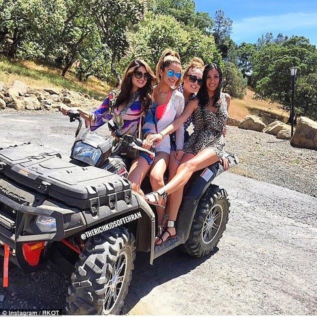 Em uma foto quatro jovens mulheres acumulam em um veículo de estilo jipe como apreciam o tempo ensolarado
