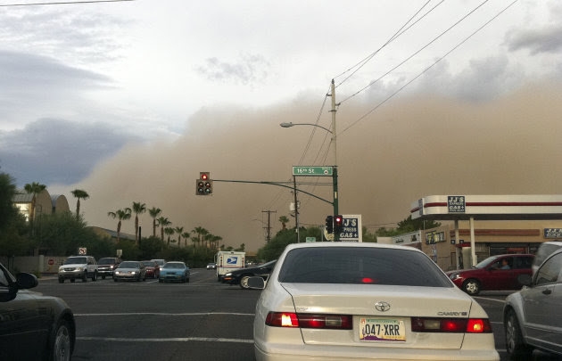 A giant wall of dust rolls through the central Phoenix area early Thursday evening, Aug. 18, 2011.  The dust storm, the third this summer, swept through the area turning the sky brown, creating danger