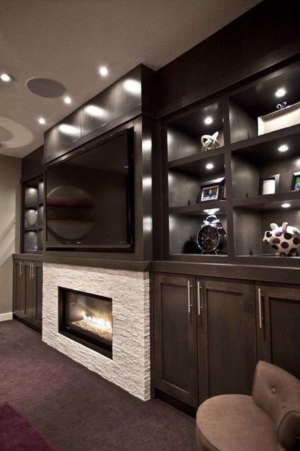 dark custom stain for the built-in maple media cabinets camouflage the TV.  stand out was the fireplace, which is surrounded with a white ledgestone marble-style tile and contrasts with the dark cabinetry.