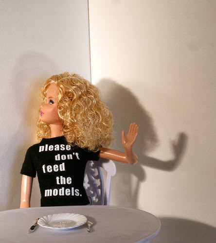 "Barbie doll wearing a shirt that says ""please don't feed the models"" seated at a table with an empty plate in front of her."