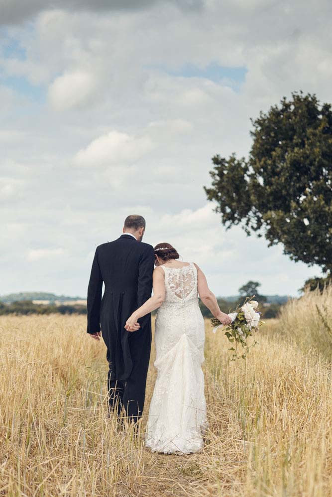 bride and groom arms in arms walking through long grass - www.helloromance.co.uk
