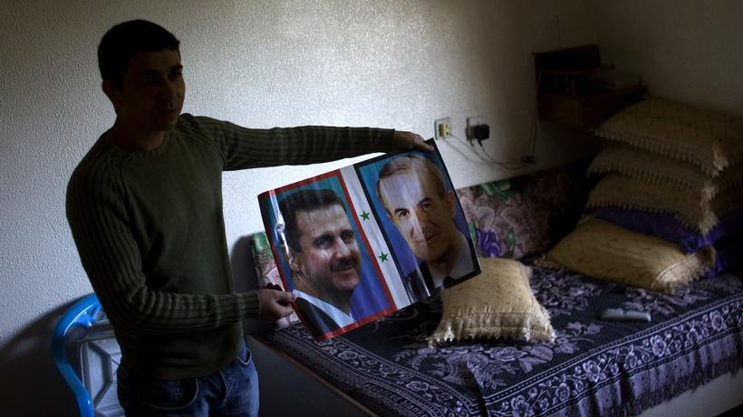 Syria: A man holds a picture of Syrias President Bashar al-Assad and his father Vater Hafez al-Assad (2010).