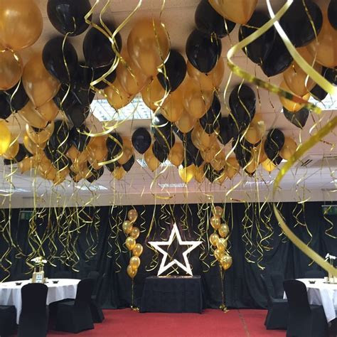 Black and gold balloon ceiling decoration with gold light