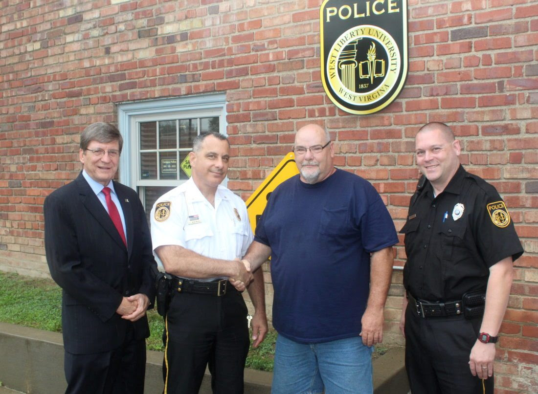 Photo Provided West Liberty University President Stephen Greiner, from left, and WLU Police Chief Joe Montemurro, West Liberty University Mayor Mark Griffith and WLU Police Officer Jim Kelso shake hands on a Police Cooperation and Mutual Assistance Agreement.