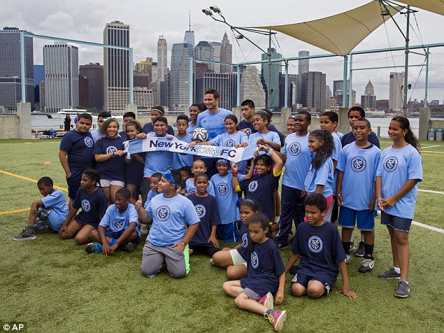 New venture: The England international poses with youngsters after his New York unveiling