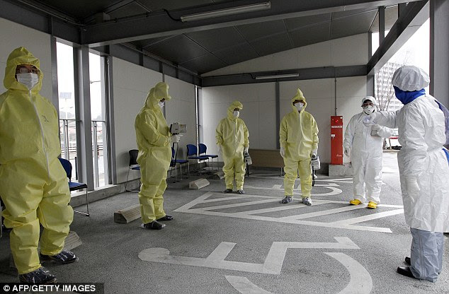Screening: Workers in radiation protection suits go through instructions before carrying out tests in Iwaki city