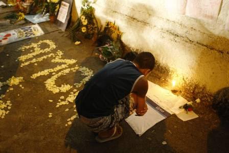 Rapaz lê as mensagens deixadas na calçada da Escola Municipal Tasso da Silveira