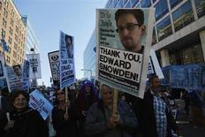 """La Agencia para la Seguridad Nacional de Estados Unidos (NSA, por sus siglas en inglés) espió más de 60 millones de llamadas telefónicas en España en poco más de un mes, según publicó el lunes el diario El Mundo, que citó documentos del organismo de espionaje norteamericano. En la imagen, unos manifestantes apoyan al excontratista de la NSA Edward Snowden, que reveló el vasto programa de espionaje de EEUU que afecta a España, en una marcha con el lema """"Dejen de observarnos: Una manifestación contra la vigilancia masiva"""" cerca del Capitolioi en Washington, el 26 de octubre de 2013. REUTERS/Jonathan Ernst"""