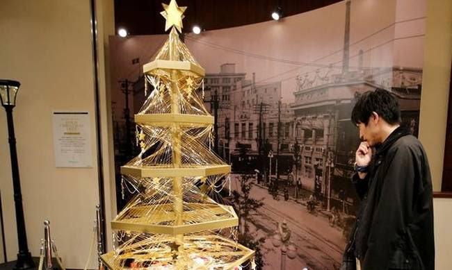 A gold Christmas tree decorated with 19 kilograms 418 lbs of pure gold wires is displayed for sa