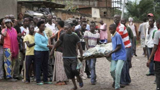 Men carry away a dead body in the Nyakabiga neighbourhood of Bujumbura