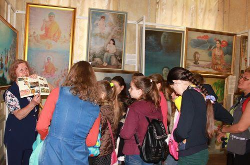 """图1:法轮功学员在乌克兰哈尔科夫市举办""""真善忍""""国际美展,传播法轮功真相。图位,参观者倾听画展导览的解说。"""