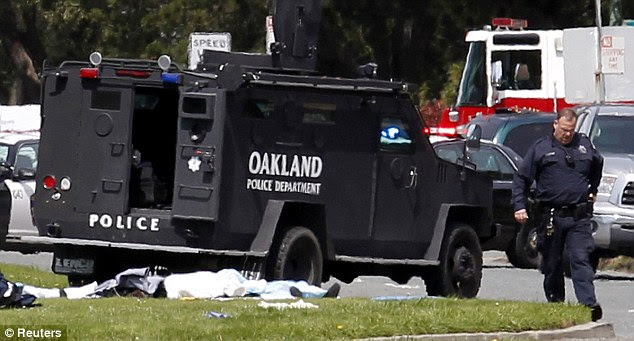 Grim: A police armored vehicle drives by what appears to be covered dead bodies following the gun attack