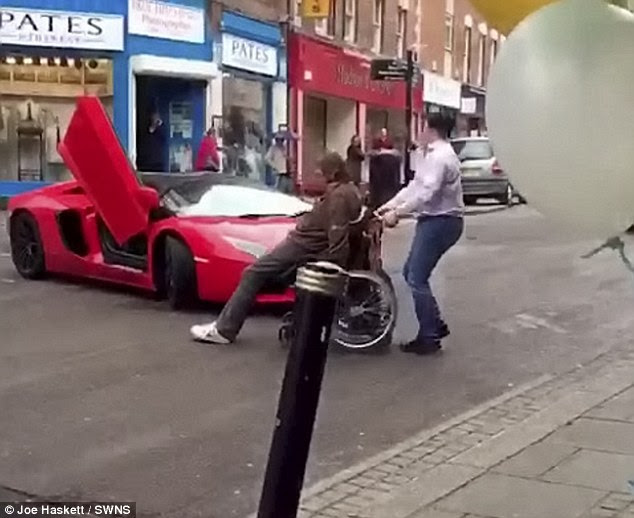 Confused and annoyed, the irate driver then tries to convince the man to move - beeping his horn repeatedly. But in the end he is forced to get out of the sports car and wheel the man to the side of the road by hand