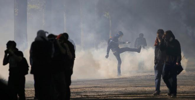 Un joven patea una granada de gas lacrimógeno durante una manifestación contra la reforma laboral francesa en Nantes, Francia. REUTERS/Stephane Mahe
