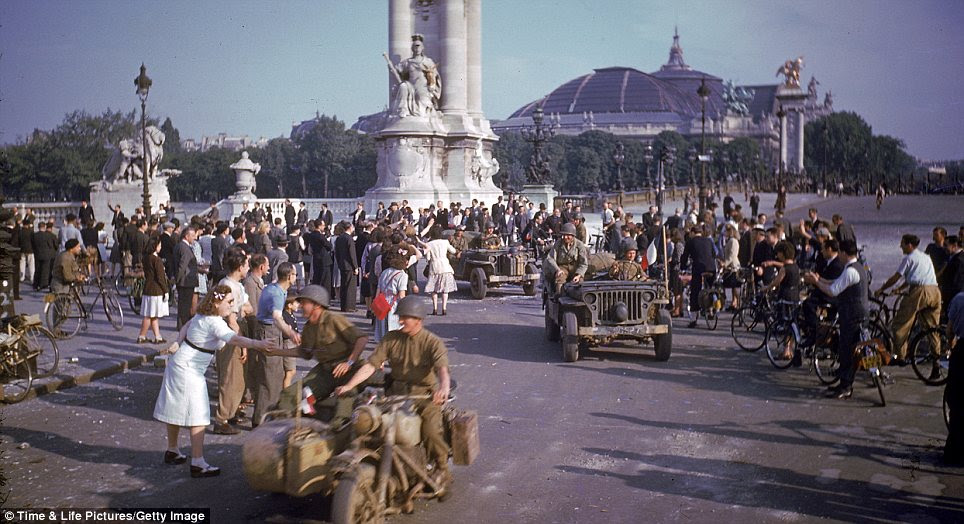 Victory: Crowds line the street to greet American soldiers after the liberation of Paris by Allied forces