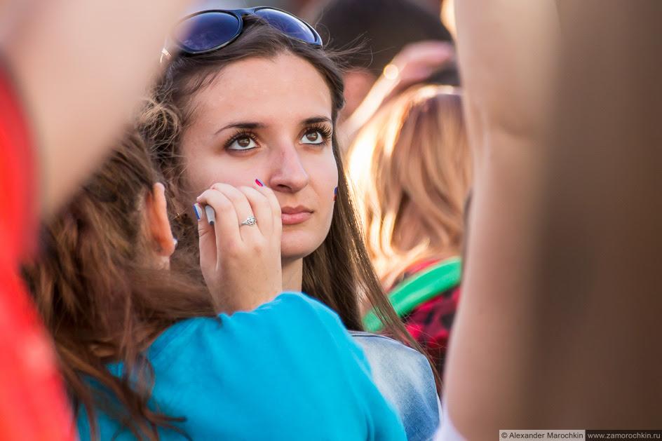 Девушке рисуют российский флаг на щеке
