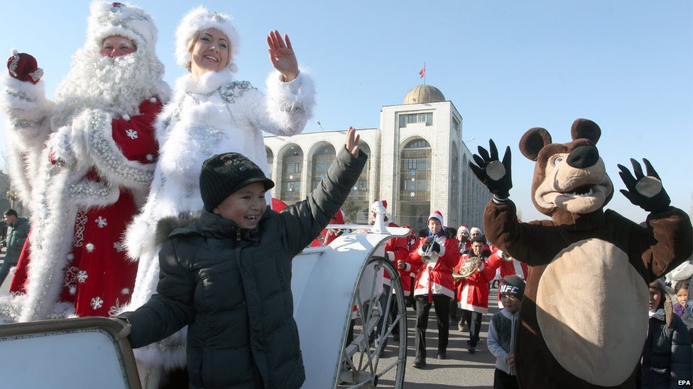 A man and a woman dressed as Father Frost (L) and his granddaughter (2-L) wave from a horse-drawn carriage as they take part in a New Year parade in Bishkek, Kyrgyzstan, 31 December 2014.