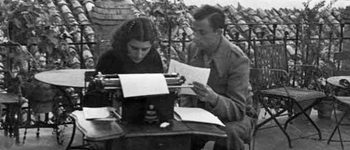Miguel Hernández y Josefina sentados al aire libre, en una terraza, escribiendo a máquina.