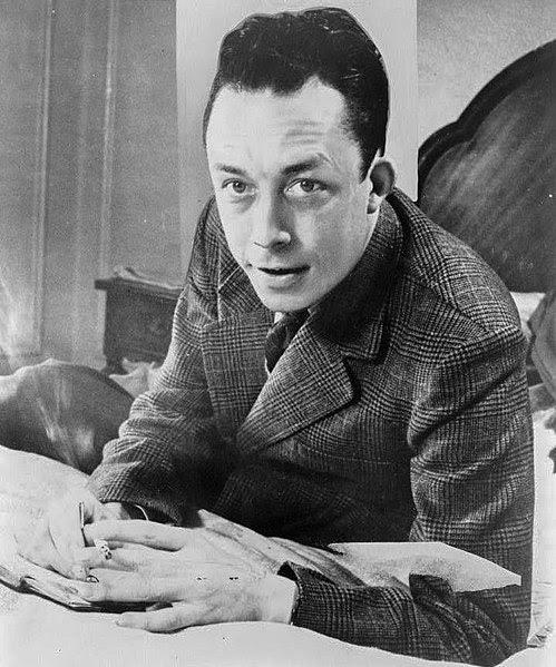 Fichier:Albert Camus, gagnant de prix Nobel, portrait en buste, posé au bureau, faisant face à gauche, cigarette de tabagisme.jpg