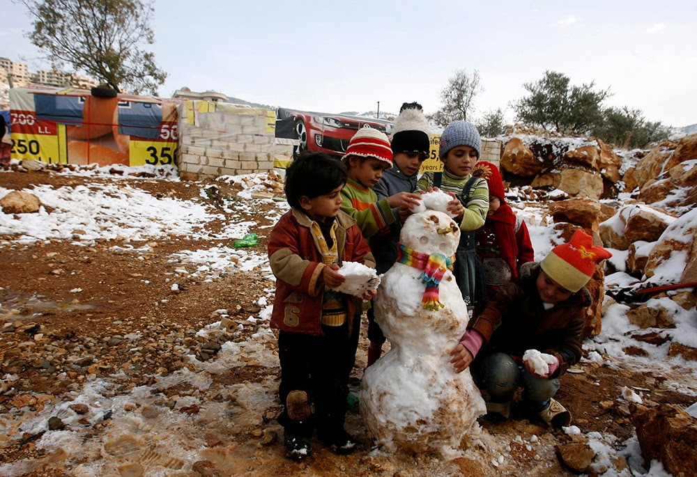 Young Syrian refugees build a snowman in a makeshift refugee camp in the Lebanese village of Baaloul in the Bekaa Valley. (MAHMOUD ZAYYAT/AFP/Getty Images)