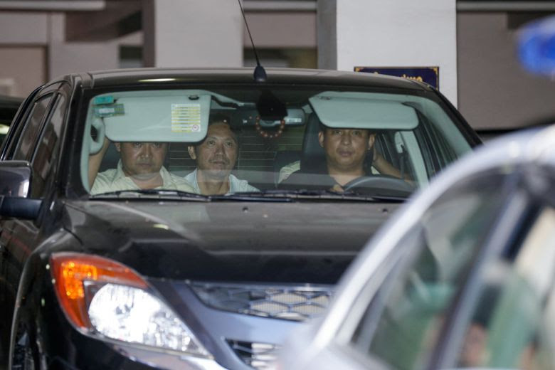 Ny Sokha (centre), head of monitoring for Adhoc, is driven out of Phnom Penh Municipal Court yesterday afternoon after being charged for bribing a witness.