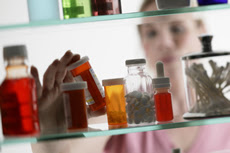Photo: woman grabbing a bottle out of a medicine cabinet