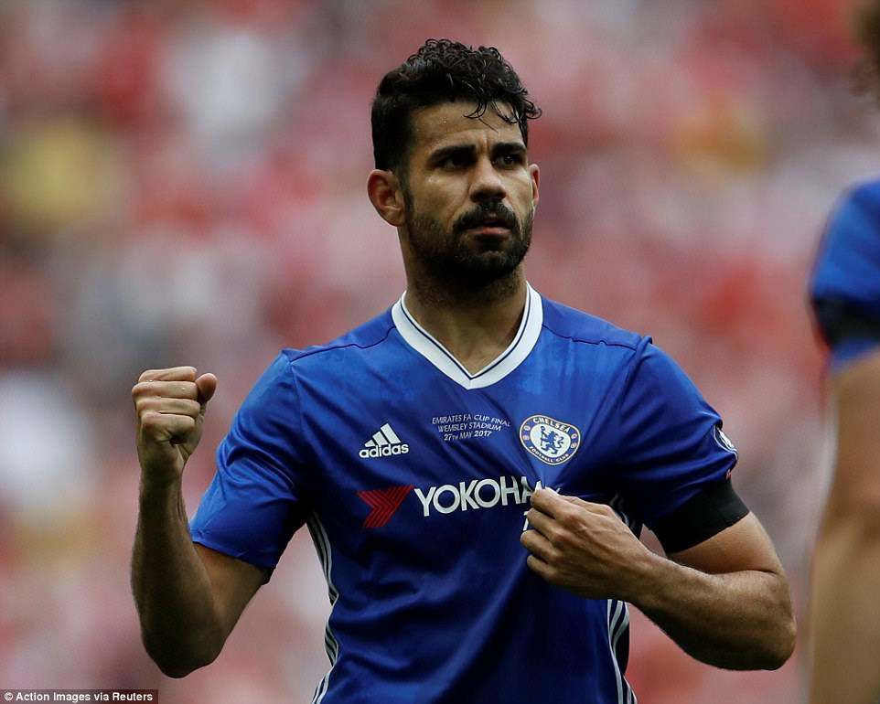 Costa grabs the Chelsea badge as he celebrates his 76th-minute goal with the west London club's supporters