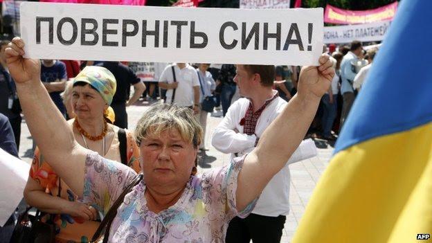 """Uma mulher ucraniana segura uma faixa com os dizeres """"trazer de volta meu filho"""" em um comício com outros parentes de oficiais e soldados ucranianos em Kiev (29 de Maio de 2014)"""