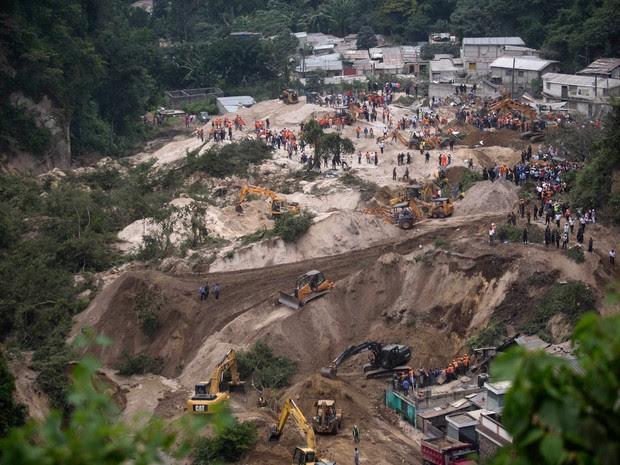 Equipes de resgate fazem busca por sobreviventes após um deslizamento de terra em Cambray, um bairro no subúrbio de Santa Catarina Pinula, a leste da Cidade da Guatemala. Uma colina desabou após fortes chuvas, enterrando várias casas  (Foto:  Moises Castillo/AP)
