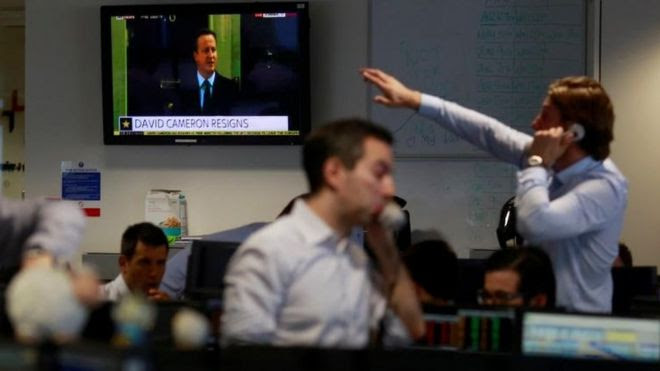 City traders in front of screen showing David Cameron's announcement