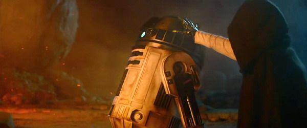 Luke Skywalker(?) lays a hand on R2-D2 in STAR WARS: THE FORCE AWAKENS.