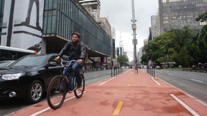 A man on a bicycle tries out the new cycle lane on Paulista Avenue