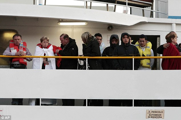 Passengers in life jackets, blankets and coats arrive on the ferry this morning following the disaster off the coast of Tuscany last night