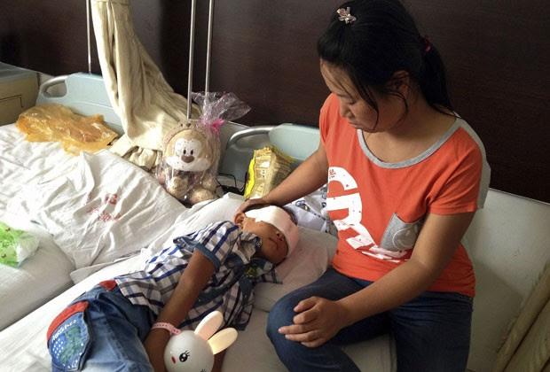Menino chinês que teve globos oculares arrancados é visto ao lado da mãe nesta quarta-feira (28) (Foto: AP)