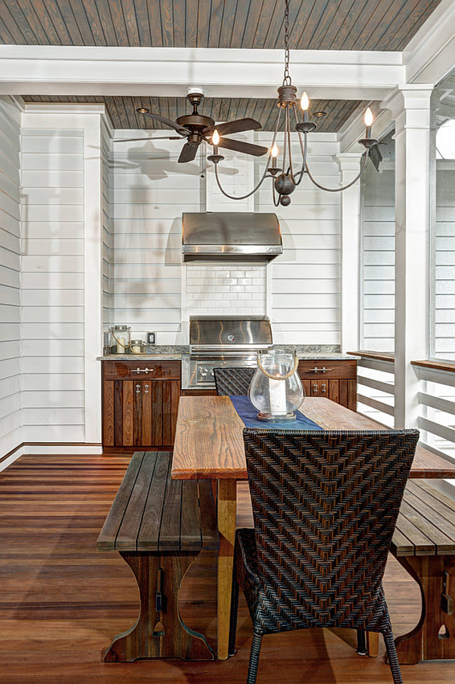 Outdoor Kitchen. Built in barbecue grill. Outdoor Ceiling Fan. Outdoor grill. Picnic table. White beam. White posts. Wicker chairs. Wood ceiling. Wood dining table
