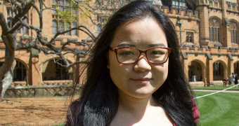 Xi Chen wears tortoise shell glasses and looks at the camera with a slight smile in the UTS quad