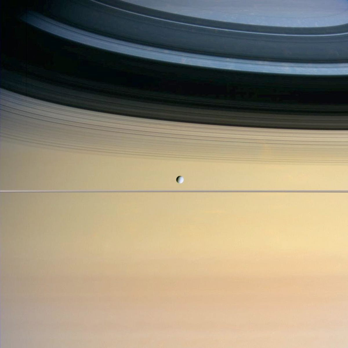 Dione, a small icy moon, is dominated by Saturn and its ring shadows in this image.